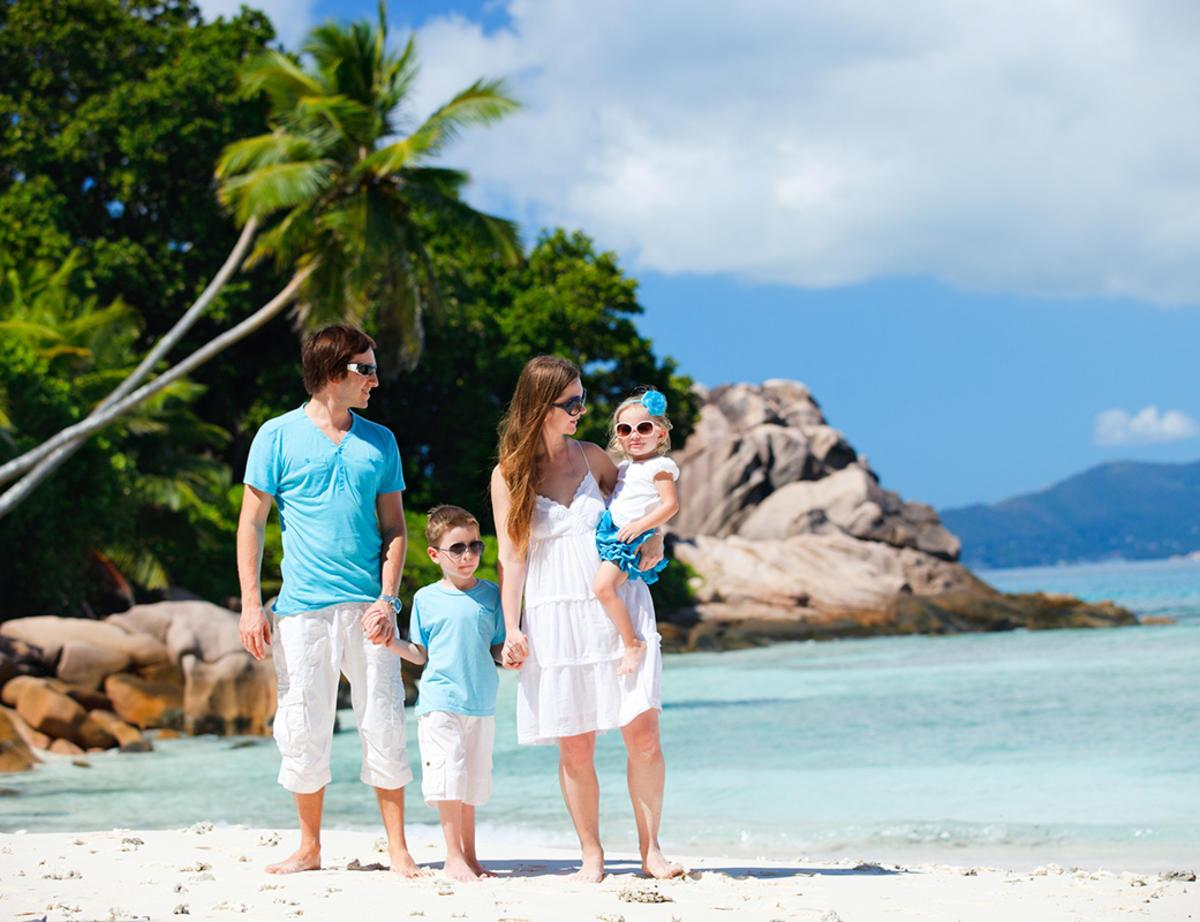 Portrait of happy young family with two kids on tropical vacation