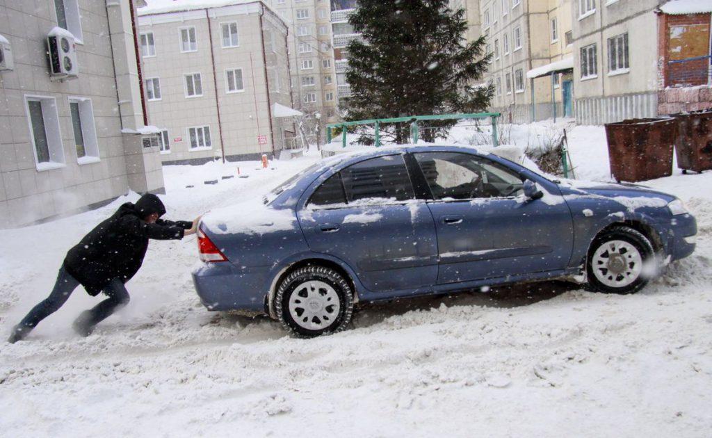 Мужчина толкает машину